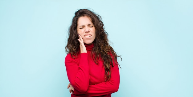 Sosteniendo la mejilla y sufriendo dolor de muelas doloroso, sintiéndose enfermo, miserable e infeliz, buscando un dentista
