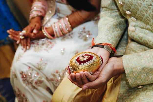 Sosteniendo el objeto sagrado de la boda india en las manos