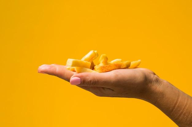 Sosteniendo papas fritas delante de fondo amarillo