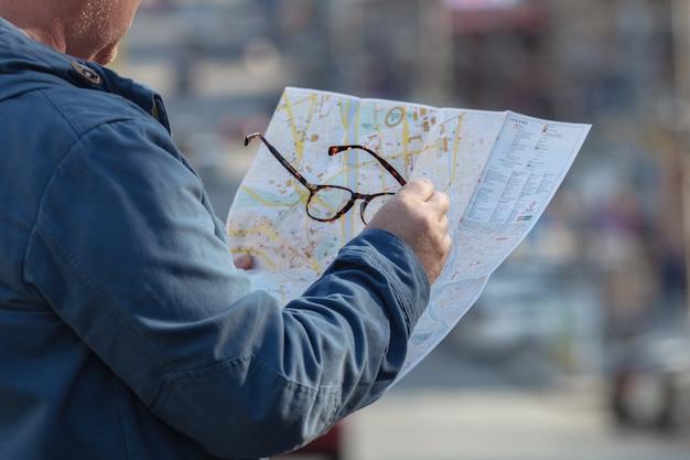 Sosteniendo papel de mapa buscando ubicación