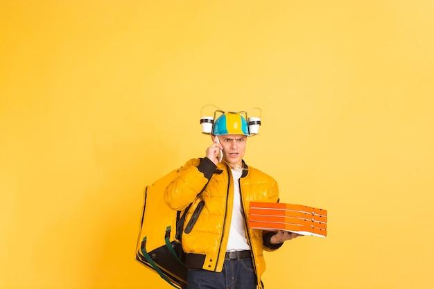 Sosteniendo pizza, hablando por teléfono. emociones del repartidor caucásico en amarillo