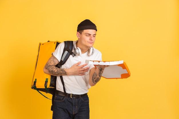 Sosteniendo pizza, huele bien. emociones del repartidor caucásico en amarillo