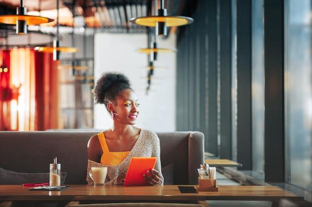 Sosteniendo tableta naranja elegante mujer con accesorios brillantes sosteniendo tableta naranja y mirando por la ventana