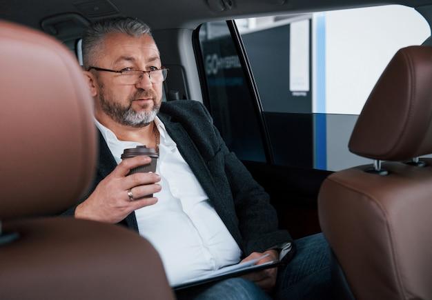 Sosteniendo una taza de café de plástico. papeleo en el asiento trasero del automóvil. hombre de negocios mayor con documentos