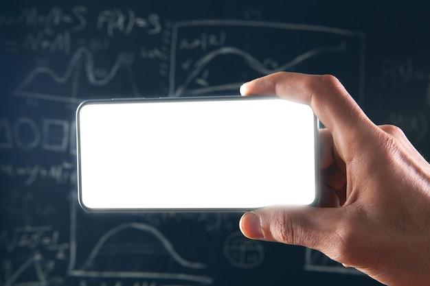 Sosteniendo un teléfono en blanco sobre un fondo de pizarra