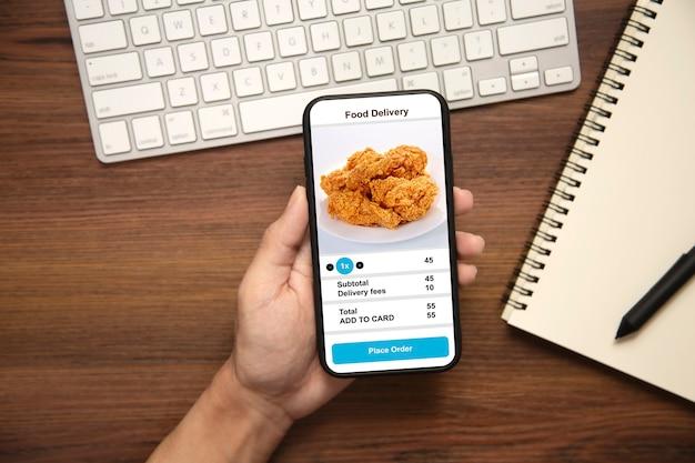 Sosteniendo el teléfono con comida de entrega de aplicación