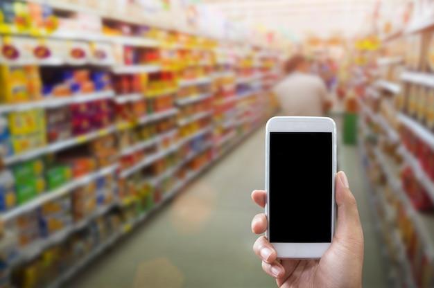 Sosteniendo el teléfono inteligente aislado sobre blanco, maqueta