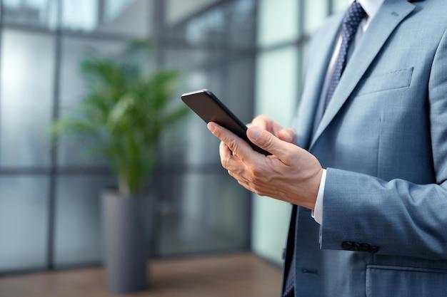Sosteniendo el teléfono inteligente negro. cerca del empresario vistiendo traje gris con smartphone negro y escribiendo mensaje