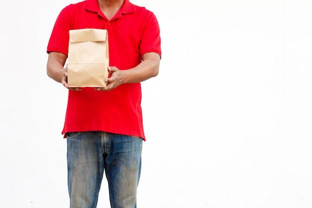 Sosteniendo varios recipientes de comida para llevar en el soporte y bolsa de papel, primer plano. fondo gris claro, lugar para insertar el texto. repartidor.