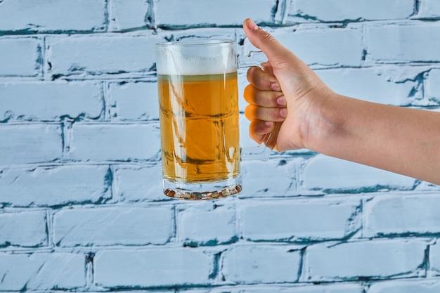 Sosteniendo un vaso de cerveza sobre un fondo azul.