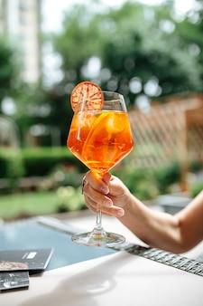 Sosteniendo un vaso de cóctel aperole spritz adornado con una rodaja de naranja