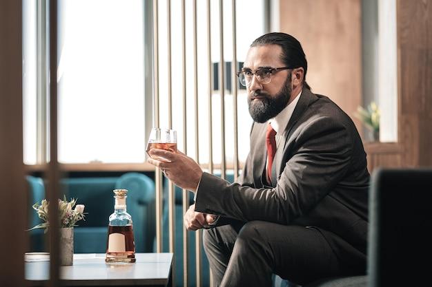Sosteniendo el vaso. hombre de negocios próspero maduro barbudo vistiendo corbata roja sosteniendo una copa de coñac sentado en un sillón