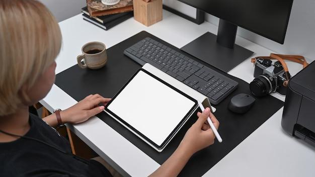 Sot recortada de joven diseñador con tableta digital mientras está sentado en la oficina.