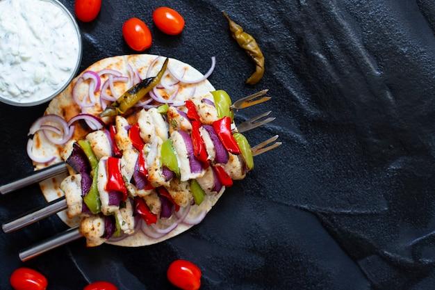 Souvlaki de pollo asado griego tradicional con salsa tzatziki y pan de pita