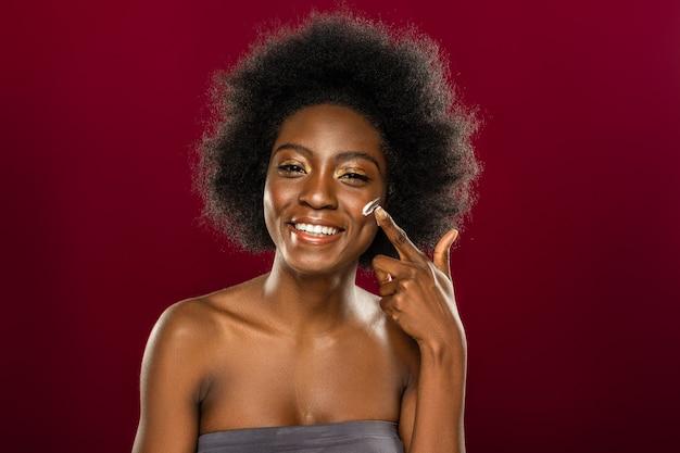 Soy hermosa. mujer joven positiva aplicando crema facial mientras quiere lucir perfecta
