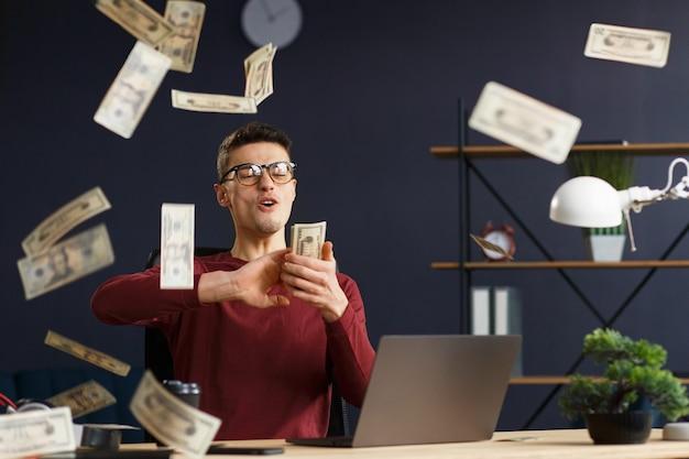 Soy rico. retrato de un joven autónomo o empresario en una oficina en casa. tira dinero en efectivo. trato exitoso. ganancias en línea. gana el dinero.