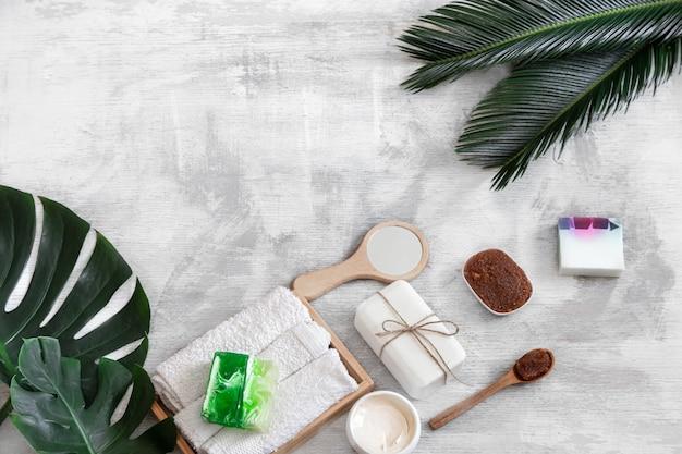 Spa. artículos de cuidado corporal en blanco con hojas tropicales.