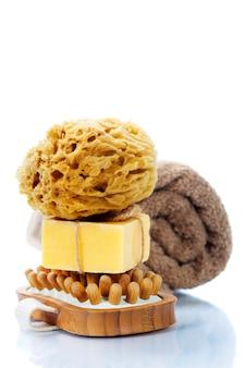 Spa y bienestar- cepillo de masaje spa anticelulítico, esponja, toalla y jabón sobre blanco