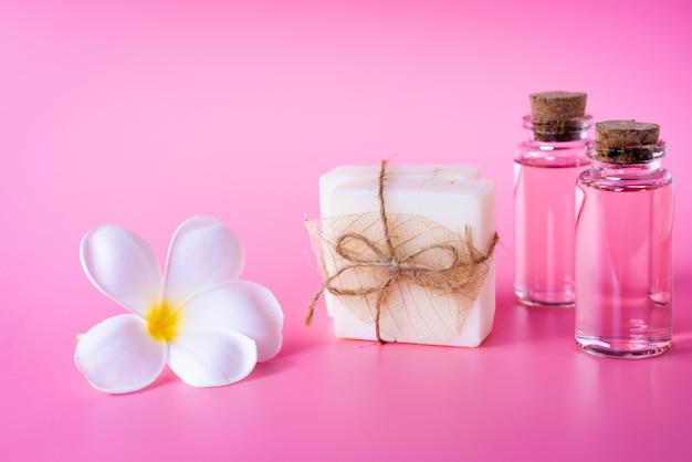 Spa de bienestar con jabón de leche, botella de aceite de rosa y hermosa flor de plumeria blanca