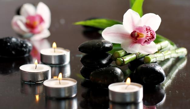Spa y bienestar, masaje con piedras y flores sobre mantel de madera