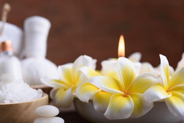 Spa de bienestar y tratamiento con aceites esenciales, piedra zen, toallas, velas, bolas de masaje auditivo y flores de frangipani en una mesa de madera con pared de ladrillo