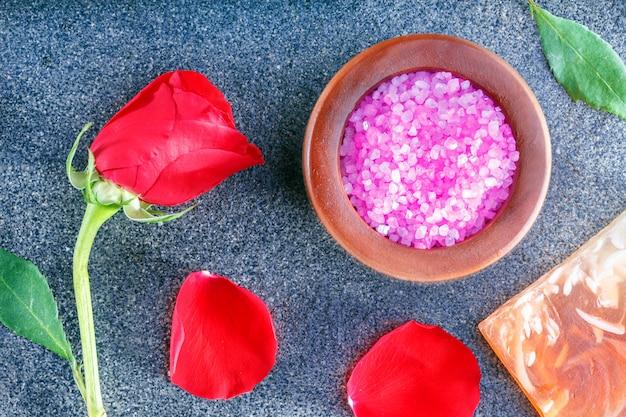 Spa bodegón con rosas, sal marina, jabón sobre baldosa cerámica. concepto de tiempo de relax vista superior