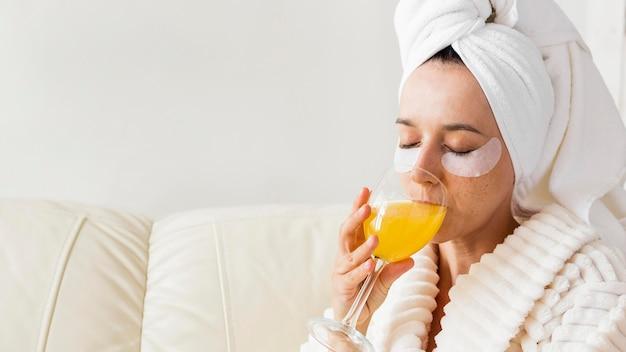Spa en casa mujer bebiendo jugo saludable de cerca