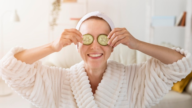 Spa en casa mujer ocultando sus ojos con rodajas de pepino