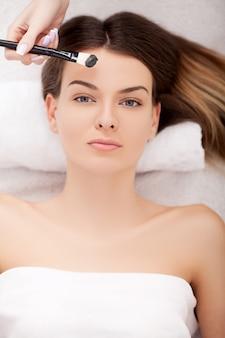 Spa. hermosa joven recibiendo un tratamiento facial en el salón de belleza.