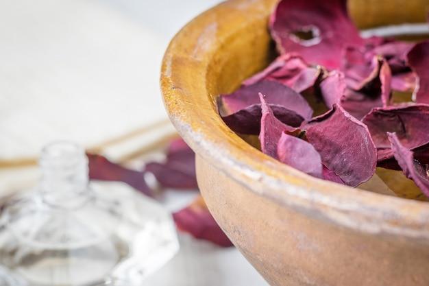 Spa con hermosos pétalos de rosa y un recipiente de arcilla.