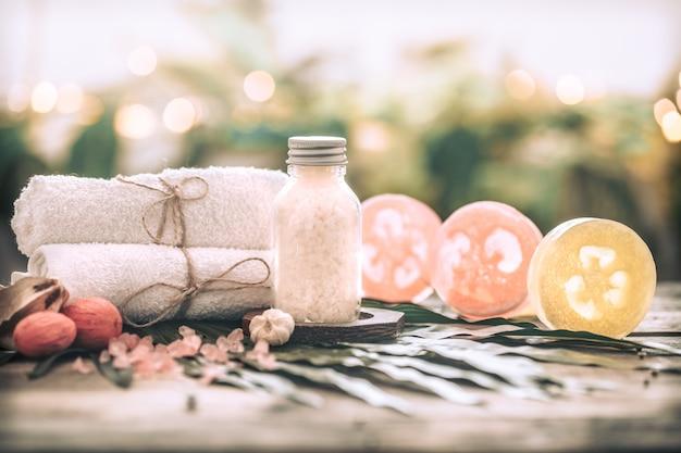 Spa jabón hecho a mano con toallas blancas y sal marina, composición en hojas tropicales, fondo de madera