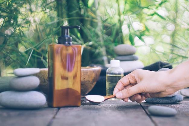 Spa con manos de mujer y agua clara sobre madera vieja.