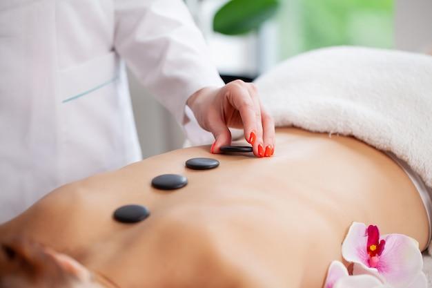 Spa masaje con piedras, hermosa mujer recibiendo spa masaje con piedras calientes en el salón de spa