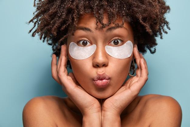 Spa mujer afroamericana con piel sana, parches blancos debajo de los ojos, toca el rostro suavemente, mantiene los labios doblados, cuida la belleza, modela sobre pared azul.