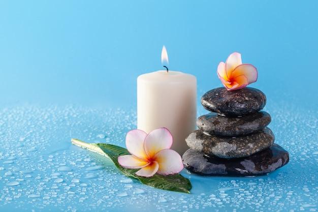 Spa pila de piedra con flores y gotas de agua sobre una pared azul
