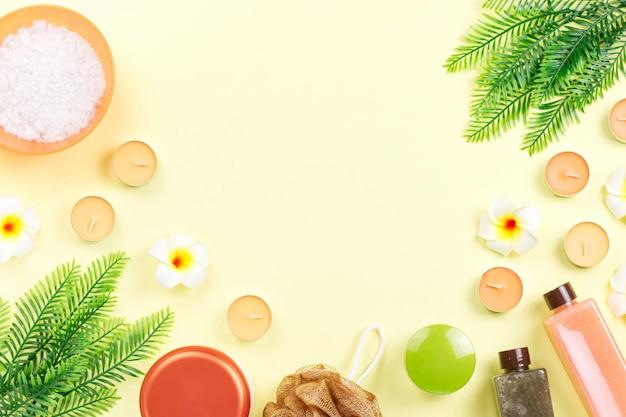 Spa y productos para el cuidado del cuerpo en plano sobre la mesa amarilla
