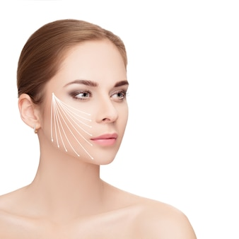 Spa retrato de mujer atractiva con flechas en su rostro sobre fondo blanco. concepto de lifting facial. tratamiento de cirugía plástica, medicina