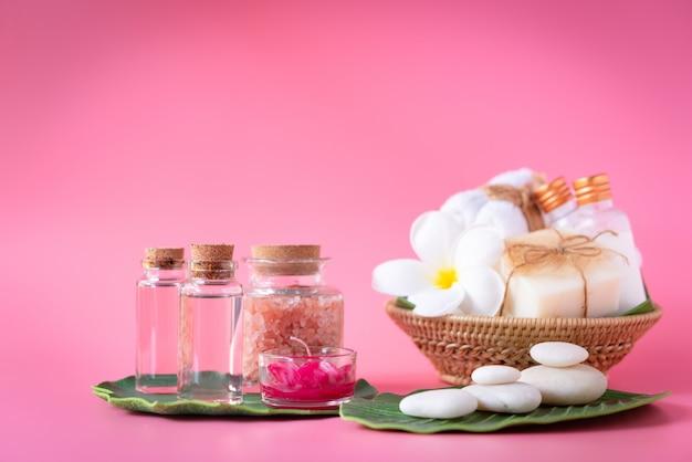 Spa sal del himalaya, vela roja, leche y jabón líquido rosa, toalla blanca, flores, piedra zen sobre hojas verdes sobre rosa