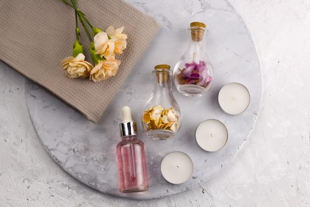 Spa set, botellas, velas y flores vista superior fondo mármol