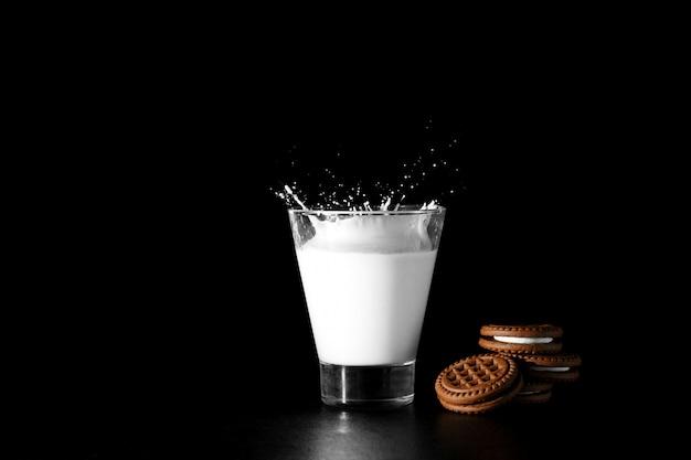 Spalsh en vaso de leche y galletas de chocolate sobre negro