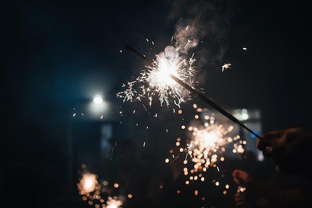 Sparkler destellos chispeantes en la mano de una persona en la celebración