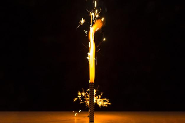 Sparkler en el escritorio para la celebración del día de la independencia contra el fondo negro