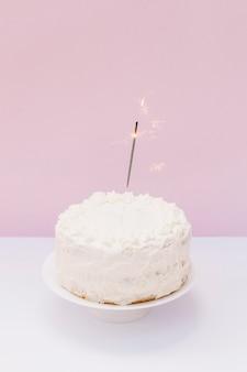 Sparkler sobre la torta de cumpleaños blanca helada en el escritorio blanco contra fondo rosado