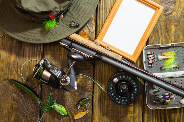 Spinning, pesca con mosca, moscas, hilanderos, sombrero y marco para su etiqueta sobre una mesa de madera.