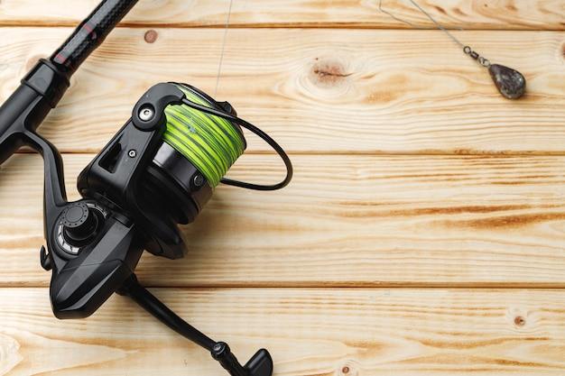 Spinning para pescar sobre fondo de madera cerrar