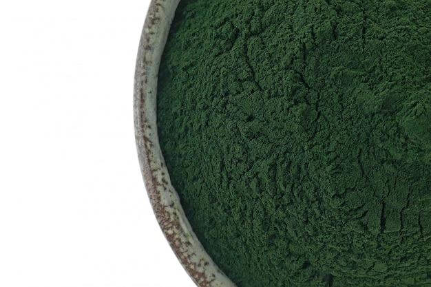 Spirulina en polvo en una taza de cerámica verde sobre un fondo blanco.
