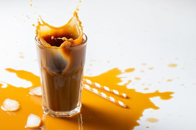 Splash de café con leche helado con cubitos de hielo y frijoles tostados