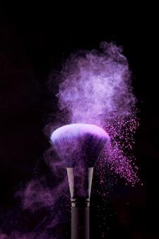 Splash de polvo púrpura en pincel de maquillaje
