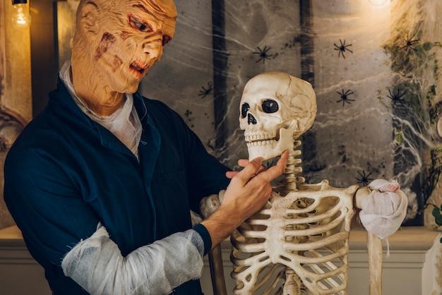 Spooky hombre posando con el esqueleto
