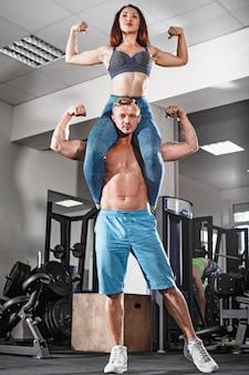 Sport fit pareja en el gimnasio. trabajar en parejas con pesas
